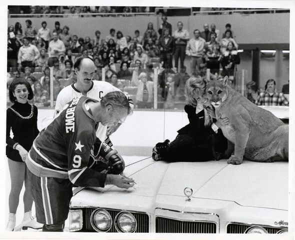 Houston Aeros Gordie Howe signs the hood of a 1973 Mercury Cougar at a WHA game