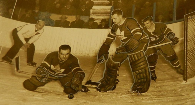 Bill Juzda clears the puck in front of Al Rollins, as Ken Mosdell looks on 1950