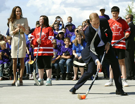Prince William shoots a ball in street hockey,  Kate watching