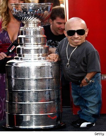 Verne Troyer stands next to The Stanley Cup